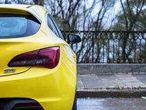 Желтое ctg astra opel припарковало около железной загородки Стоковое Фото