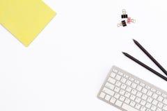 Желтые блокнот, клавиатура компьютера, 2 черный карандаш и зажимы для бумаги на белой предпосылке минимальная концепция настольно Стоковая Фотография