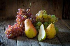 Желтые груши и ветвь зрелых органических виноградин на деревянном backgro Стоковое Изображение RF