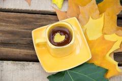 Желтые лист на чашке чаю с листьями осени на деревянном Стоковые Изображения