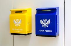 Желтые и голубые коробки столба на стене рядом с почтовым отделением стоковые фото