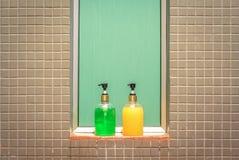 Желтые и зеленые бутылки жидкостного мыла и шампуня в ванной комнате Стоковая Фотография