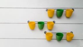 Желтые и зеленые цветочные горшки висят на рельсе Стоковое Фото