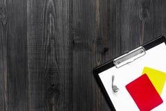 Желтые и красные карточки и свисток рефери на деревянном copyspace взгляд сверху предпосылки Стоковые Фото