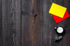 Желтые и красные карточки рефери, секундомер и свисток на деревянном copyspace взгляд сверху предпосылки Стоковая Фотография RF