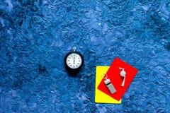 Желтые и красные карточки, секундомер, свисток на голубом copyspace взгляд сверху предпосылки таблицы Стоковая Фотография