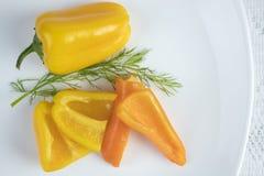 Желтые и оранжевые перцы на плите Стоковые Изображения RF