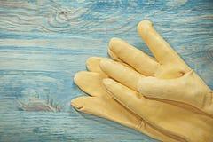 Желтые кожаные работая перчатки на conce конструкции деревянной доски Стоковые Фото