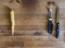 Желтые морковь, нож и peeler, подготовка еды Стоковая Фотография RF
