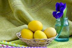 Желтые пасхальные яйца в корзине и голубой радужке Стоковые Изображения