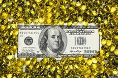 Желтые пилюльки и 100 долларов банкноты Стоковые Фотографии RF