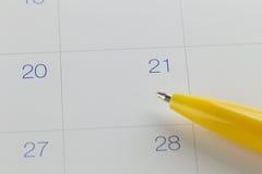желтые пункты ручки к 21 на предпосылке календаря Стоковые Фото