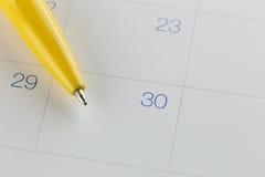 желтые пункты ручки к 30 на предпосылке календаря Стоковые Изображения RF