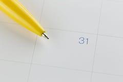 желтые пункты ручки к 31 на предпосылке календаря Стоковая Фотография RF