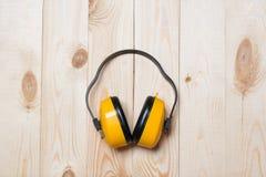 Желтые работая защитные наушники на деревянном столе Стоковое Изображение