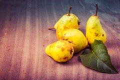 Желтые сезонные груши с лист на предпосылке старых доск Стоковое Фото