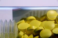 Желтые таблетки в стеклянной бутылке Стоковое Фото