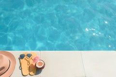 Желтые тапочки с питьем и крышкой около воды Стоковые Изображения RF