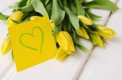 Желтые тюльпаны на белых досках стоковые изображения rf