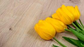 Желтые тюльпаны на деревянном столе, предпосылке пасхи Стоковая Фотография RF