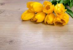 Желтые тюльпаны на деревянном столе, предпосылке пасхи Стоковое Изображение RF