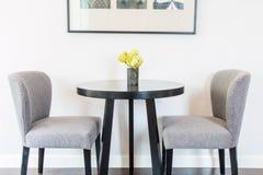Желтые цветки в вазах на таблице и стулья стеной Стоковое Изображение RF