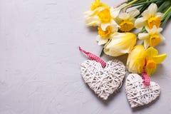 Желтые цветки и 2 декоративных сердца на сером текстурированном backgr Стоковые Изображения RF