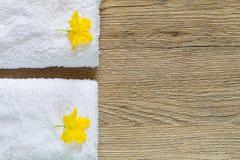 Желтые цветки на белых полотенцах с мягкой тенью на винтажной деревянной предпосылке Стоковая Фотография RF