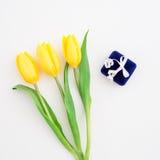 Желтые цветки тюльпана и коробка кольца на белой предпосылке Плоское положение, взгляд сверху Стоковое Изображение RF