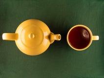 Желтые чайник и кружка с чаем, космосом экземпляра Стоковые Фото