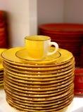 желтые чашка и поддонник с плитами Стоковые Изображения