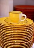 желтые чашка и поддонник с плитами Стоковые Фото