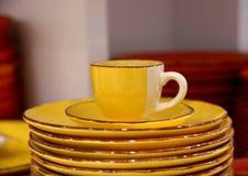 желтые чашка и поддонник с плитами Стоковое Фото