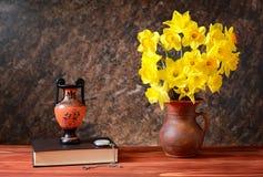 Желтые daffodils в керамической вазе, amphorae и книгах Стоковые Фото
