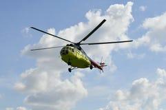 Желтый вертолет MI-8 летает против облаков Стоковые Изображения