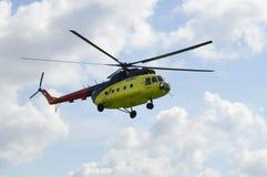 Желтый вертолет MI-8 летает против облаков Стоковые Фотографии RF