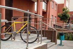 Желтый велосипед на шагах около мусорного бака стоковое изображение rf