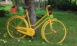 Желтый велосипед с цветками стоит в саде Стоковое Фото