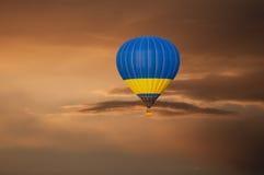 Желтый голубой горячий воздушный шар в полете на заход солнца Стоковая Фотография