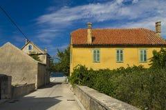 Желтый деревенский дом в Zlarin Стоковые Фотографии RF