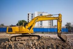 желтый затяжелитель backhoe на строительной площадке и работе стоковое изображение