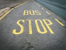 Желтый знак автобусной остановки покрашенный на асфальте дороги Стоковое Изображение