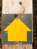 Желтый знак наконечника стрелы указывая вверх на деревянный график столба стоковое изображение rf