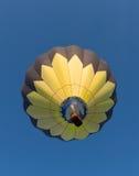 Желтый и черный воздушный шар в полете стоковые изображения