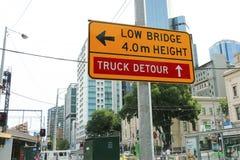 Желтый и черный мост 'Low, 4m Height' и 'Truck Detour' подписывают около моста рельса улицы щепок стоковые изображения