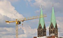 Желтый кран перед 2 шпилями собора, голубое небо, облака стоковые изображения rf