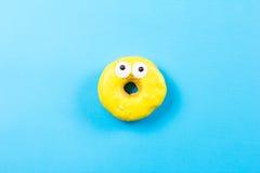 Желтый круглый донут с глазами на голубой предпосылке Плоское положение, взгляд сверху Стоковое фото RF