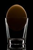 Желтый макрос конца-вверх пасхального яйца в стеклянной чашке, на задней части черноты Стоковые Фото
