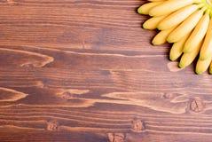 Желтый младенец бананов вниз с его вентилятором на коричневой доске в верхней части Стоковое Изображение RF
