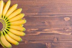 Желтый младенец бананов наклоняет вверх по левому вентилятору на коричневой доске к r Стоковое Изображение